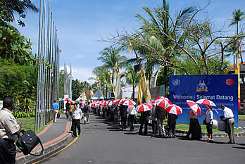 Using umbrellas as sun shields, participants wait to be security checked