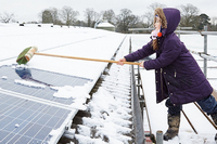 Girl clears snow from a solar panel using a broom