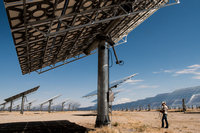 Person standing under a very large solar panel on solar farm